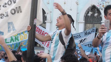 fan fest : MOSCOW, RUSSIA, JUNE 20, 2018: Soccer World Cup Argentine football fans with flags at the on Nikolskaya Street, One of the fans climbed the pole and chanted the slogan. Crowd with mobile phones and action cameras in their hands Stock Footage