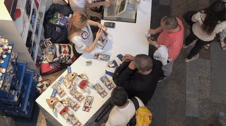 atributo : MOSCOW, RUSSIA - AUGUST 5, 2018: Tourists buy official souvenirs - Zabivaka toy in the point of sale of sports store in GUM, Moscow. Video was taken from above
