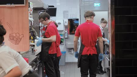 organizing : Moscow, Russia - September 16, 2018: Men and Women Works in the Kitchen Fast Food Restaurant Chain. McDonalds Kitchen Staff in the working process. Workflow Kitchen Fast Food Cafe