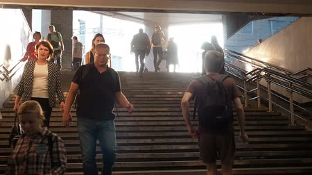 approaching subway : Moscow, Russia - September 6, 2018: Ordinary people go up and go down to the underground subway at rush hour. People go down to the underpass. Silhouettes of people walking down the steps against the backdrop of the sun.