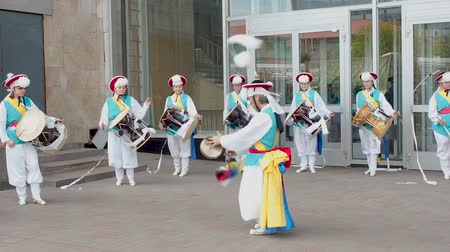 nori : Moscow, Russia, July 12, 2018: Korean culture festival. A group of musicians and dancers in bright colored suits perform traditional South Korean folk dance Samul nori Samullori or Pungmul and play percussion Korean musical instruments. Musician hits theK Stock Footage