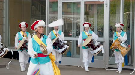 dobos : Moscow, Russia, July 12, 2018: Korean culture festival. A group of musicians and dancers in bright colored suits perform traditional South Korean folk dance Samul nori Samullori or Pungmul and play percussion Korean musical instruments. Musician hits theK Stock mozgókép