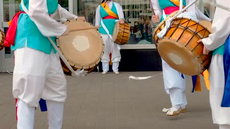 taiko drums : Moscow, Russia, July 12, 2018: Korean culture festival. A group of musicians and dancers in bright colored suits perform traditional South Korean folk dance Samul nori Samullori or Pungmul and play percussion Korean musical instruments