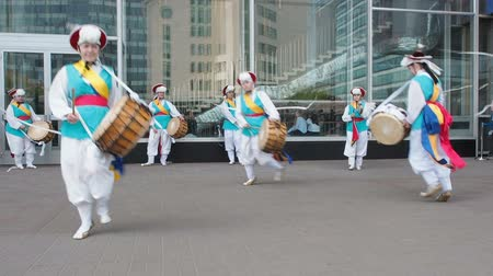 nori : Moscow, Russia, July 12, 2018: Korean culture festival. A group of musicians and dancers in bright colored suits perform traditional South Korean folk dance Samul nori Samullori or Pungmul and play percussion Korean musical instruments. Musicians hits the