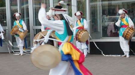 taiko drums : Moscow, Russia, July 12, 2018: Korean culture festival. A group of musicians and dancers in bright colored suits perform traditional South Korean folk dance Samul nori Samullori or Pungmul and play percussion Korean musical instruments. Musician hits the