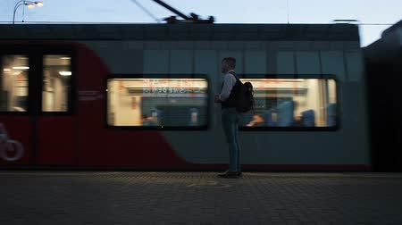 nyel : Moscow, Russia - August 20, 2018: The man is waiting for the train at the subway station in the evening. People approach the carriages of the approaching train. Train departure of the Moscow Central Circle