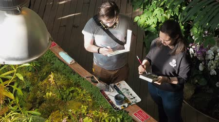 guache : Moscow, Russia, April 17, 2019: Young people artists paint plants with watercolors in the botanical garden talking on different topics gesticulating
