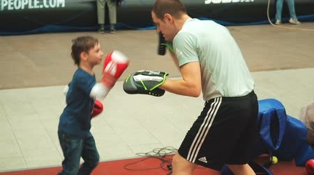 ring de boxe : Moscow, Russia - April 12, 2019: Cute boy training with coach and in boxing gym first time. Little boy in boxing gloves is boxing with his teacher