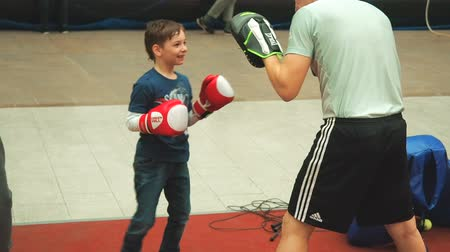 kickbox : Moscow, Russia - April 12, 2019: Cute boy training with coach and in boxing gym first time. Little boy in boxing gloves is boxing with his teacher