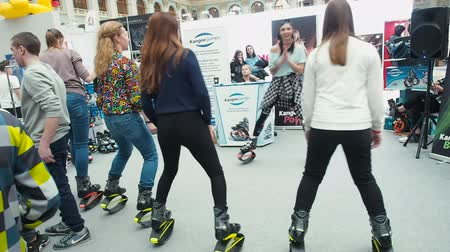 canguru : Moscow, Russia - April 12, 2019: Younh girl team in Kangaroo jumps anti gravity fitness boots doing endurance exercises at gym indoor. People are running on the spot in jumper boots. Female in leggings and in kangoo jump boots with springs are dancing on