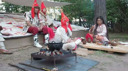 stile impero : Moscow, Russia - August 20, 2018: Reenactment festival in Moscow Times and epochs . Location: Scythia of Herodotus. People asian appearance dressed in costumes arrange a feast in the open air near the hearth demonstrating culture and life of the Scythian Filmati Stock