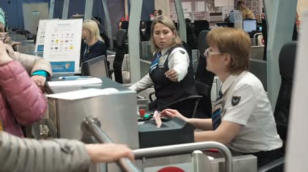 obramowanie : Moscow, Russia - May 6, 2019: Two female airport security personnel checking identification at a check-in or boarding counter at the departure terminal holding the passports of two male passengers. Passengers check-in. Employee checks passport information Wideo
