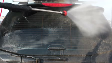 water sprayer : MOSCOW, RUSSIA MARCH 25, 2019: Slow Motion Video of a Car Washing Process on a Self-Service Car Wash. A Jet of Water With a High Pressure Wash Off the Dirt From the Car Rear Window. Foamed Detergent Drains From the Surface of the Car Body