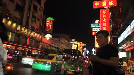 busz : Bangkok, Thailand - May 8, 2019: The movement of cars and people in the night asian city. Lights of a big city. Chinatown is the big market shopping and foods on the street. Street Food Shopping Area, Yaowarat Road. Night life with many people and traffic
