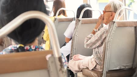 emeryt : Bangkok, Thailand - May 25, 2019: Asian senior man sitting in the lotus position in a motor vehicle seat and thinking about something in tram while sunny morning. People ride the bus