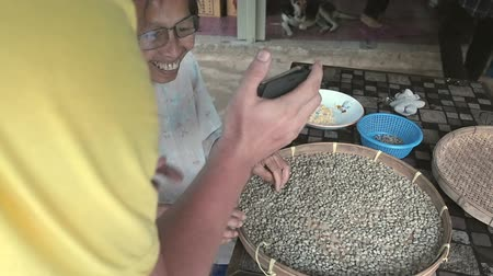 bamboo basket : Chiang Mai province, Thailand - May 23, 2019: A man shows something to the elderly woman on the screen of a smartphone, she smiles in process sorting through arabica coffee beans in small round wicker basket or bamboo sieve, make quality control and selec