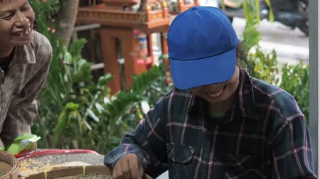 bamboo basket : Chiang Mai province, Thailand - May 23, 2019: Positive smiling people sorting through arabica coffee beans in small round wicker basket or bamboo sieve, quality control and selection on coffee plantation factory of Southeast Asia. manual labor in collecti