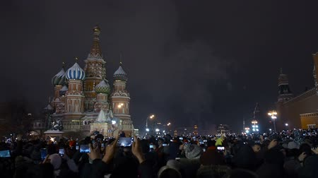 kreml : Moscow, Russia -January 1, 2019: Many people gathered for a universal celebration New Years in Moscow. Fireworks on Red Square near the Spasskaya Tower on New Years Eve. Multicolored salute in the Kremlin. A large crowd of people celebrates on Red Square