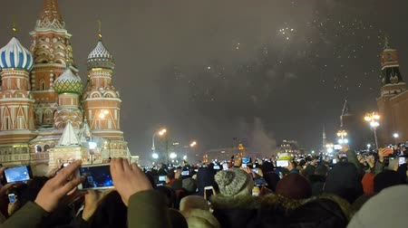 cremlino : Moscow, Russia -January 1, 2019: Many people gathered for a universal celebration New Years in Moscow. Fireworks on Red Square near the Spasskaya Tower on New Years Eve. Multicolored salute in the Kremlin. A large crowd of people celebrates on Red Square