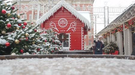 adorno : Moscow, Russia -January 1, 2019: Smiling dancing teens are photographed on the fairy christmas street decorations background - Golden and red balls hanging on the Christmas tree covered with snow and red Gingerbread house. Beautiful decorated street for C Vídeos