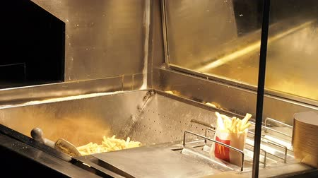 frites : Bangkok , Thailand - May 23, 2019: Woman frying potato in McDonalds, Fast food french fries cooking in deep fryer Stock Footage