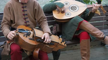 lira : Moscow, Russia - June 13, 2019: Times and Epochs Festival. Street musicians dressed in vintage ethnic oriental clothes play music on traditional Middle Eastern musical instruments turkish hurdy-gurdy and oud. The video footage contains sound