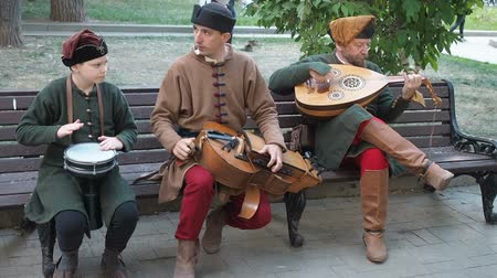 lira : Moscow, Russia - June 13, 2019: Times and Epochs Festival. Street musicians dressed in vintage ethnic oriental clothes play music on traditional Middle Eastern musical instruments turkish darbuka, hurdy-gurdy and oud. The video footage contains sound Stok Video