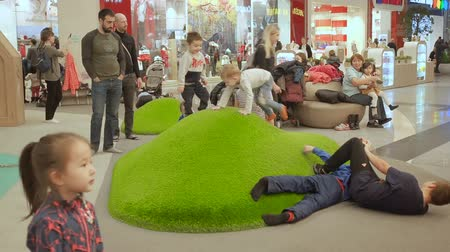 Moscow, Russia - November 11, 2019: Boys have fun and fooling around on the hill with artificial grass. Kids plaing in the play area of the shopping center. Playful Children frolic in the gaming zone of the shopping center.