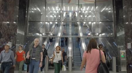 Moscow, Russia - September 11, 2019: People go up and go down to the underground subway. Modern metro station and hurrying people of the big city. Contemporary subway station. The movement of diversity people in the subway. Стоковые видеозаписи