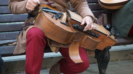 lira : Moscow, Russia - June 13, 2019: Street musician dressed in vintage ethnic oriental clothes play music on traditional Middle Eastern musical instrument hurdy-gurdy also named wheel fiddle, wheel vielle. Contains sound