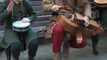 lira : Moscow, Russia - June 13, 2019: Street musicians dressed in vintage ethnic oriental clothes play music on traditional Middle Eastern musical instruments turkish darbuka and hurdy-gurdy. The video footage contains sound