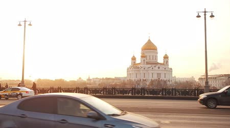 Moscow, Russia - November 23, 2019: View from Big Stone Bridge to the Cathedral of Christ the Savior in Moscow in the sunset golden time. Traffic in a big city. The movement of cars on a broadband highway in a metropolis. Dramatic light in the evening. Sm