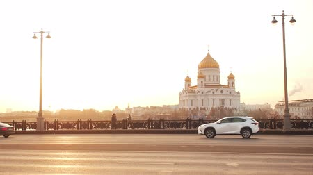 мостовая : Moscow, Russia - November 23, 2019: View from Big Stone Bridge to the Cathedral of Christ the Savior in Moscow in the sunset golden time. Traffic in a big city. The movement of cars on a broadband highway in a metropolis. Dramatic light in the evening. Sm