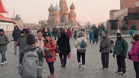 MOSCOW, RUSSIA – November 23, 2019: Chinese tourists take pictures in the Kremlin on the Moscow sights background near the Spasskaya Tower and St. Basils Cathedral
