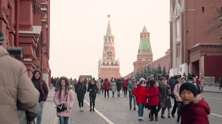 convidado : MOSCOW, RUSSIA - NOVEMBER 23, 2019: Muscovites and guests of the capital of Russia walks on the Kremlin passage, looks at the sights of Moscow. Spasskaya Tower on background