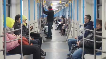 MOSCOW, RUSSIA - NOVEMBER 21, 2019: Movement of metro train carriag. People in warm clothes sitting in underground carriage an using smartphones. A man sitting thinking about something, Girl and woman surfing wifi in smartphone. Train with through passage