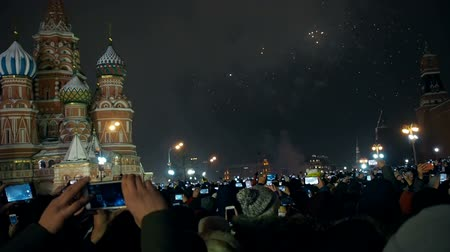 csillagszóró : Moscow, Russia -January 1, 2019: Many people gathered for a universal celebration New Years in Moscow. Fireworks on Red Square near the Spasskaya Tower on New Years Eve. Multicolored salute in the Kremlin. A large crowd of people celebrates on Red Square