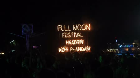 KOH PHANGAN, THAILAND - DECEMBER 22, 2018 : Full Moon Party fire sign on Haad Rin beach in island Koh Phangan, Thailand. Girls and guys dance in Full Moon party on the sandy beach near fire signboard
