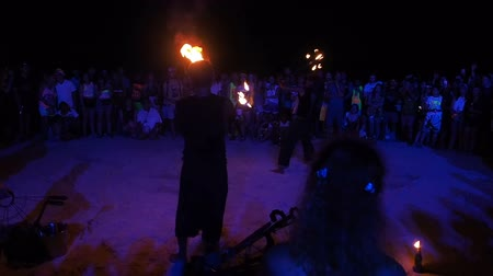 Koh Phangan, Thailand, May 19, 2019: Guys and girls crawl under the crossbar with fire in night on sand beach, fire show in Full Moon party in island Koh Phangan, Thailand