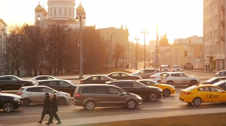 Moscow, Russia - November 23, 2019: Moscow at the beautiful sunset and golden hour. Cathedral of Christ the Saviou Borovitskaya Square view. Traffic in a big city. The movement of cars on a broadband highway in a metropolis. Dramatic light in the evening.