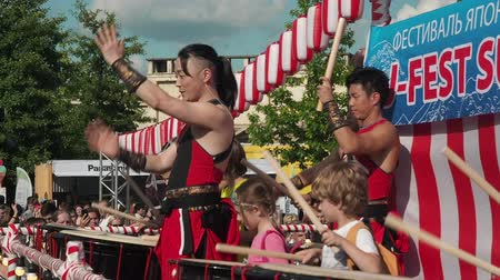 grão : Moscow, Russia - July 21, 2019: Japanese taiko artist teaches children to play on the taiko drums on scene during the japanese festival J-fest Stock Footage