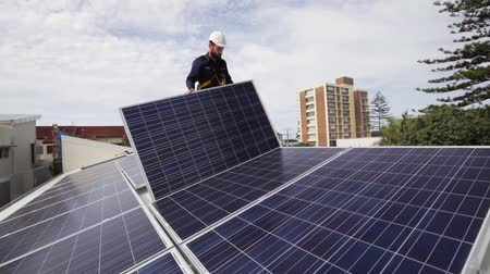 устанавливать : Solar technician installing solar panels on roof.
