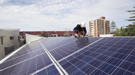 fotovoltaica : Solar technician installing solar panels on roof.