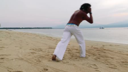 sztuki walki : Brazilian capoeira dancer training on the beach at sunrise.