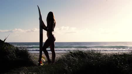 серфер : Attractive girl standing with surfboard on beach at sunrise. Slide. Slow motion. Стоковые видеозаписи