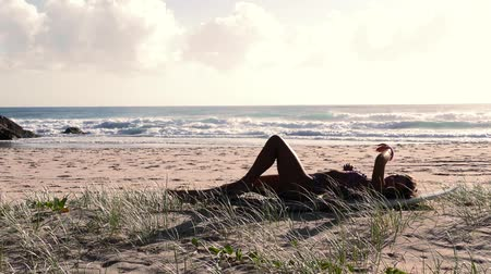 prancha de surfe : Attractive girl on surfboard relaxing on beach at sunrise. Slow motion.