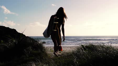 szörfös : Surfer girl walking to beach with surfboard at sunrise. Slow motion. Stock mozgókép