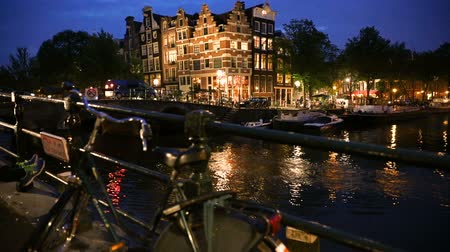 Amsterdam canal at dusk with bikes and boats