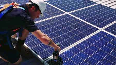 casa verde : Solar panel technician with drill installing solar panels on roof on a sunny day