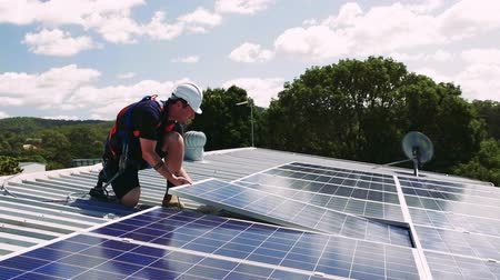 installer : Solar panel technician with drill installing solar panels on roof on a sunny day
